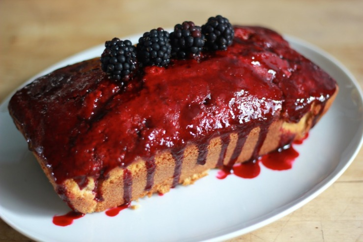 A picture of a cake with blackberry glaze and fresh blackberries